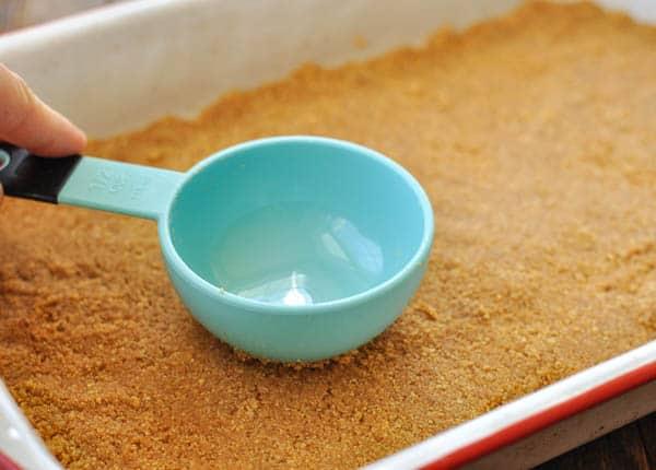 Pressing graham cracker crumbs into baking dish