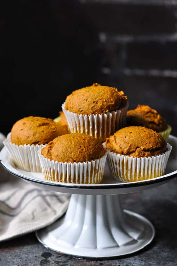 Front shot of homemade pumpkin muffins on a cake stand in front of a dark background
