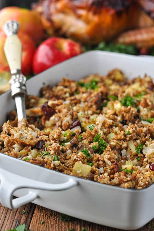 Side shot of a spoon in a dish of the best sausage and apple stuffing recipe