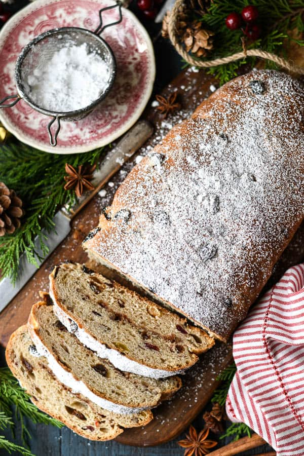 Overhead image of a loaf of stollen bread on a cutting board surrounded by Christmas decorations
