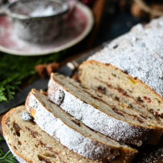 Close up front shot of a stollen recipe on a cutting board topped with powdered sugar