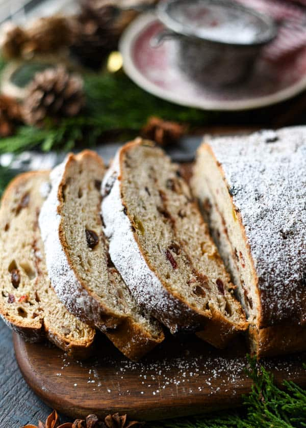 Side shot of a sliced loaf of Christmas Stollen on a cutting board