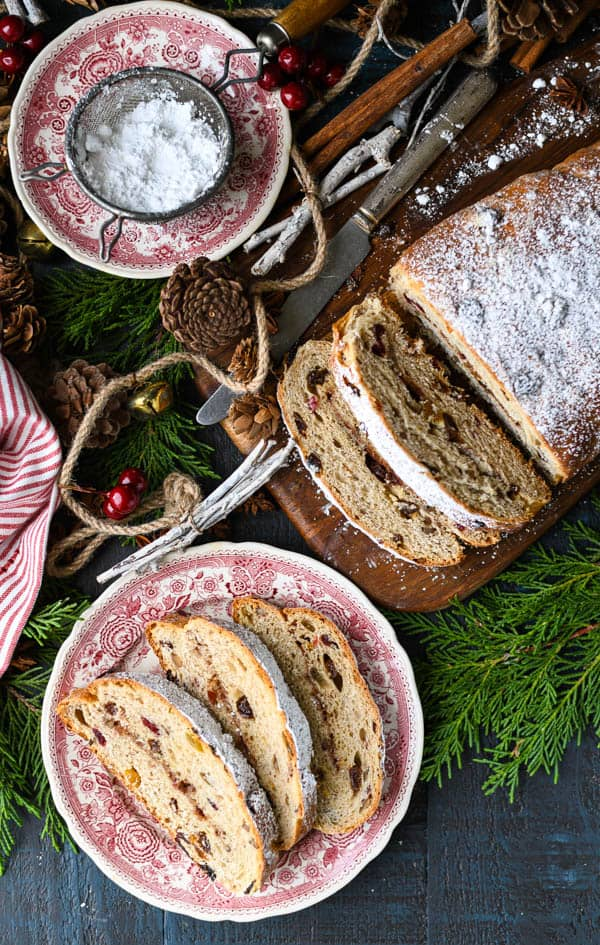 Overhead shot of three slices of stollen on a plate with the larger loaf nearby
