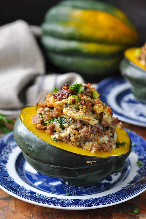Side shot of stuffed acorn squash on a blue and white plate