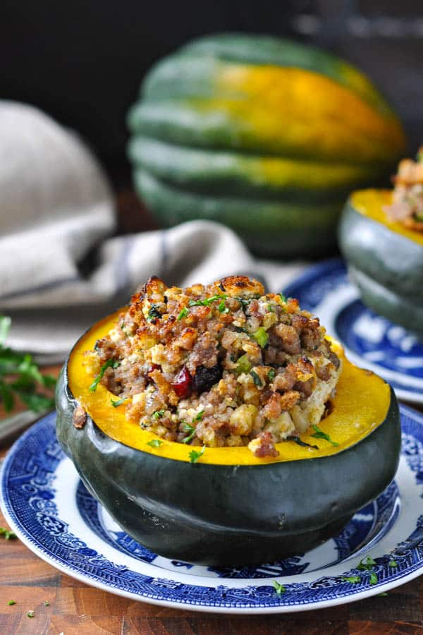 Side shot of a half of cranberry and apple stuffed acorn squash garnished with parsley