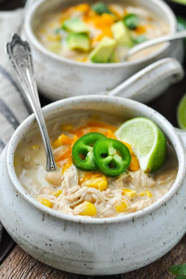 Close up front shot of a bowl of white chicken chili with cheese jalapeno and lime on top