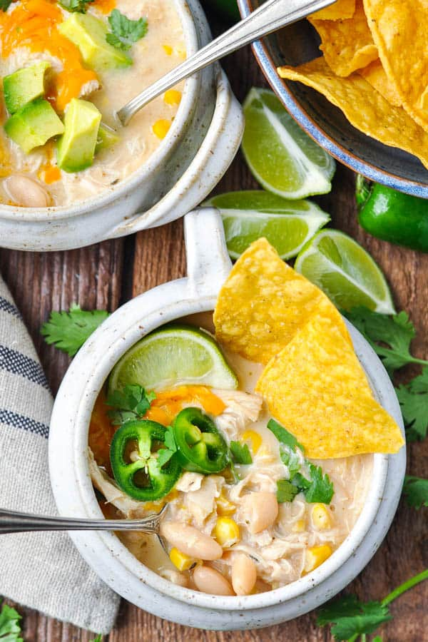 Close overhead image of a bowl of creamy white bean chicken chili with toppings