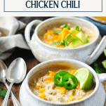 Side shot of two bowls of easy white bean chicken chili and a text title box at top