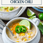 Front shot of a bowl of stovetop white bean chicken chili with text title overlay
