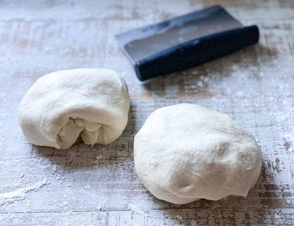 Process shot of dividing dough to shape a baguette
