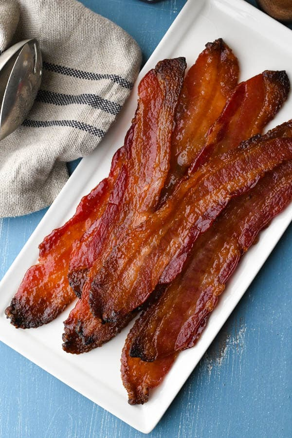 Close overhead image of candied bacon on a white rectangular platter