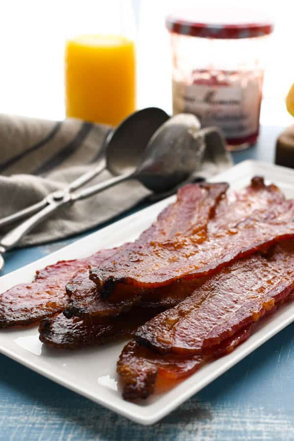 Side shot of a platter of quick candied bacon on a brunch table