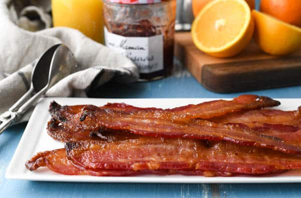 Horizontal side shot of candied bacon on a white tray