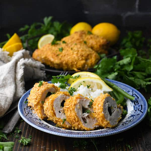 Square shot of an easy baked chicken kiev recipe served on a blue and white plate with fresh herbs and lemon
