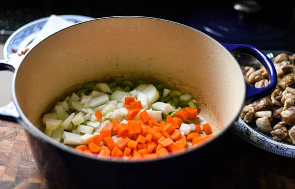 Add vegetables to a pot of chicken stew
