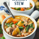 Front shot of a bowl of chicken stew with text title box at top