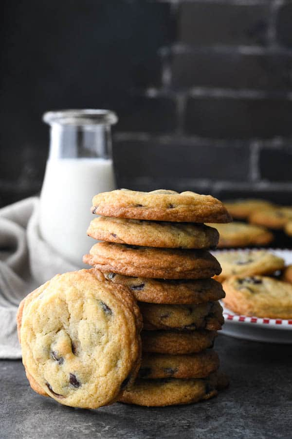 Stack of chewy chocolate chip cookies with milk in the background