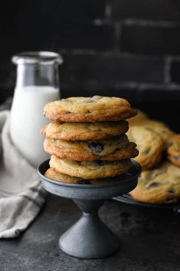 Stack of thick, soft and chewy chocolate chip cookies in front of a glass of milk