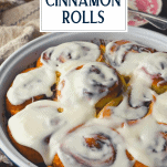 Side shot of pan of cinnamon rolls with cream cheese frosting and text title overlay