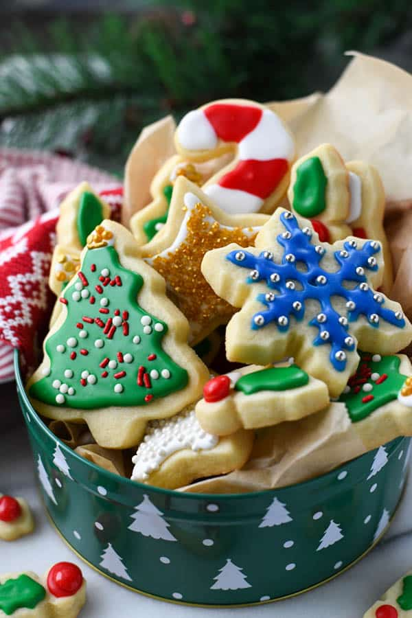 Cookie tin full of cut out sugar cookies in Christmas shapes