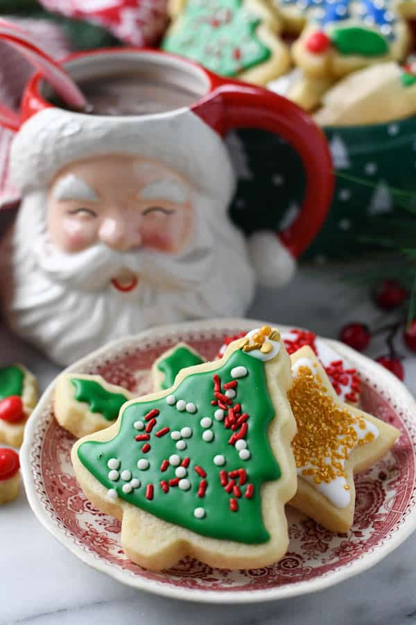 Plate of cut out sugar cookies with hot cocoa in the background