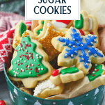 Cookie tin full of Christmas cut out sugar cookies with text title overlay