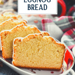 Front shot of sliced eggnog quick bread on a plate with text title overlay