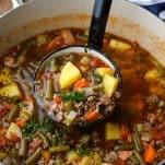 Close up shot of a ladle serving Hamburger Soup from a big pot