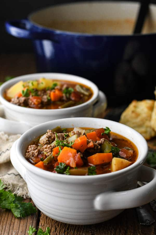 Side shot of old fashioned vegetable beef soup recipe served in white bowls