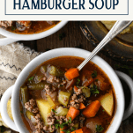 Overhead shot of a bowl of hamburger vegetable soup with text title box at top