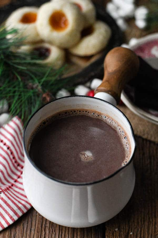 Homemade hot chocolate recipe prepared in a white saucepan