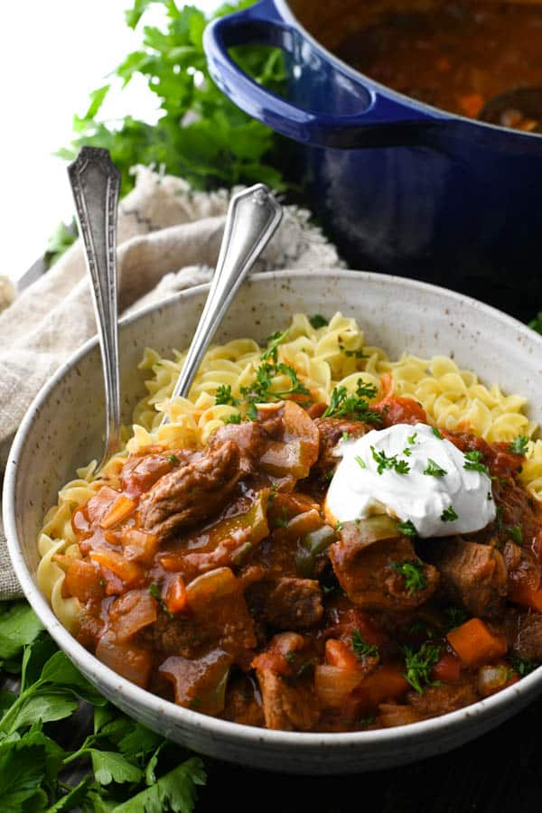 Close up side shot of a bowl of Hungarian Goulash with a dollop of sour cream on top