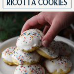 Hand picking up a ricotta cookie with a text title box at the top