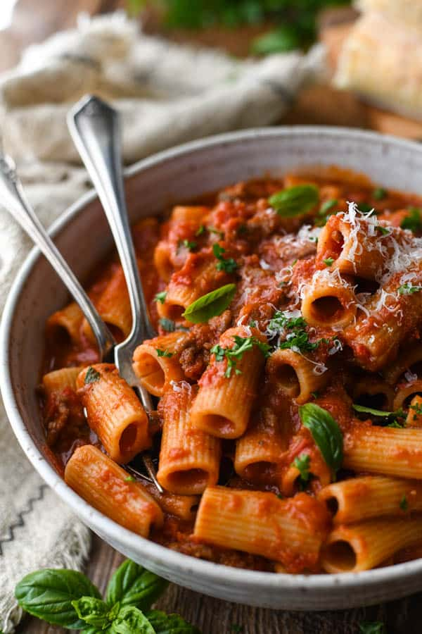Close up front shot of a bowl of Italian Sausage Pasta with fresh grated Parmesan