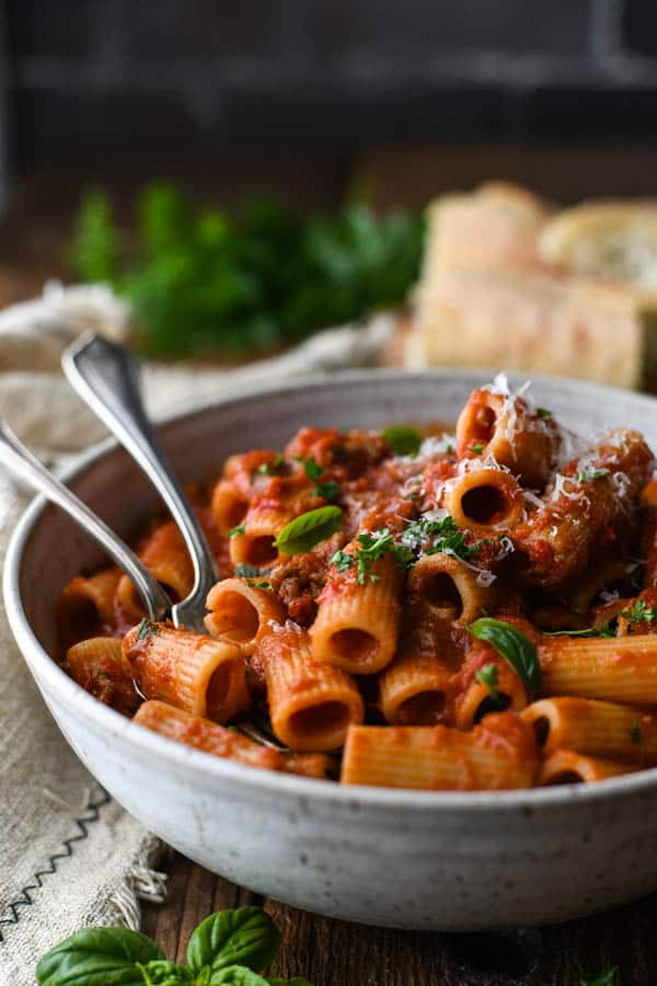 Close up side shot of a bowl of Italian Sausage and Pasta in a white bowl
