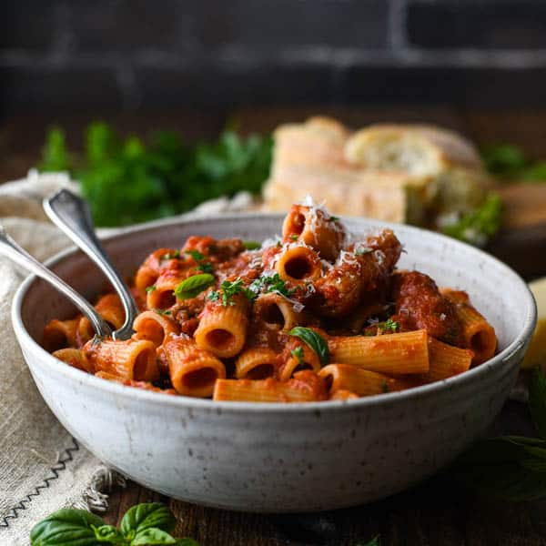 Square image of a bowl of Italian sausage pasta