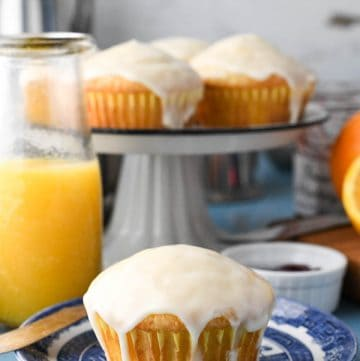 Glaze orange muffin on a blue and white plate with a carafe of orange juice in the background