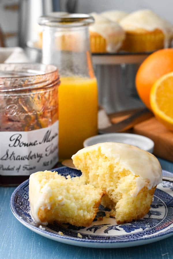 Split orange muffin on a plate with a jar of jam