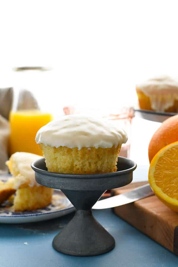 Glazed orange muffin on a small cake stand
