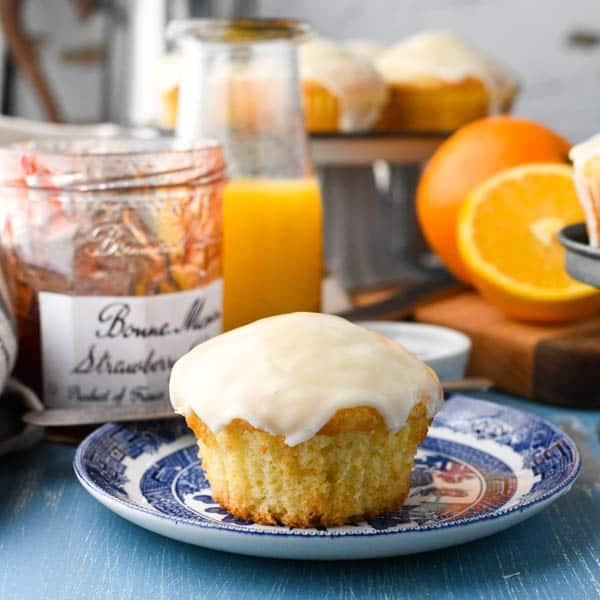 Square image of orange muffins served on a breakfast table