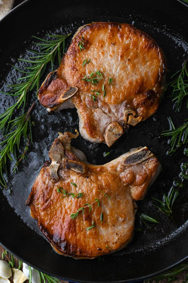 Fried pork chops with herbs in a skillet