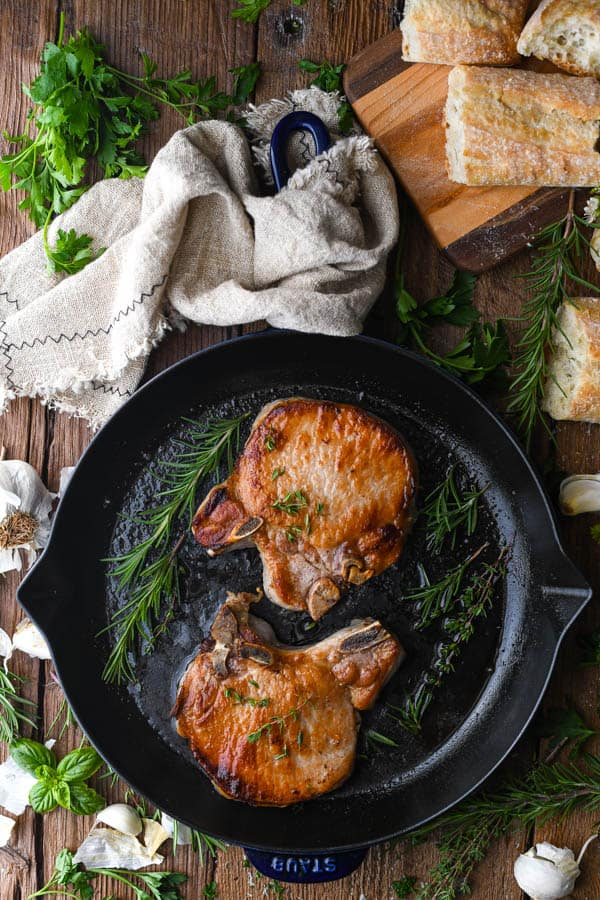 Overhead shot of garlic and rosemary pork chops in a cast iron skillet
