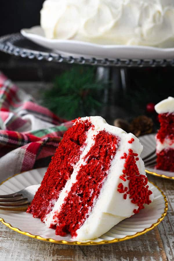 Close up front shot of a big slice of the best Southern red velvet cake recipe served on a plate on a white table
