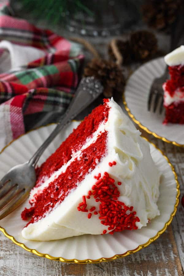 Front shot of a slice of easy red velvet cake recipe with cream cheese frosting