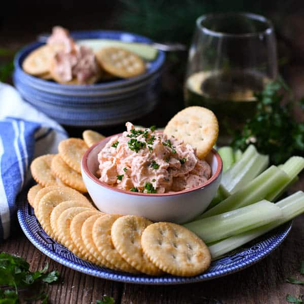 Square image of easy shrimp dip served with a glass of wine
