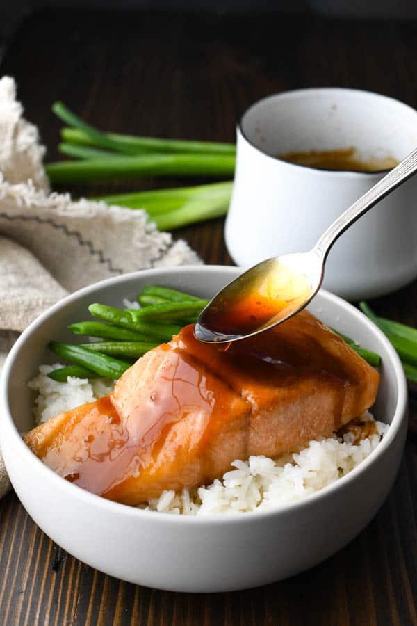 Spooning teriyaki glaze over a piece of baked salmon