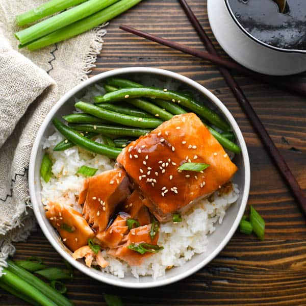 Square overhead shot of a bowl of teriyaki salmon with rice and green beans