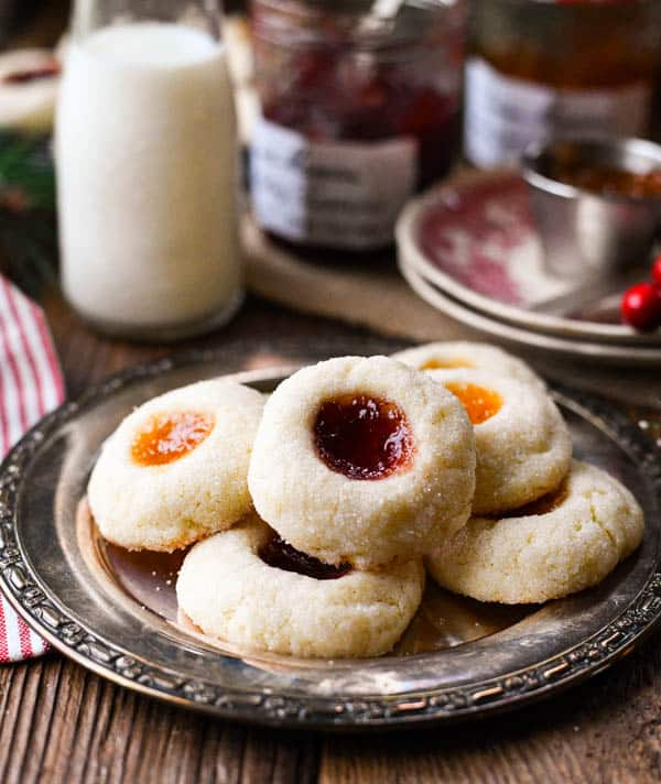 Front shot of a platter of thumbprint cookies on a wooden table with jam in the background