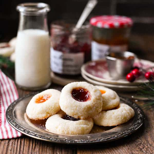 Square image of a plate of easy thumbprint cookies with milk and jam in the background