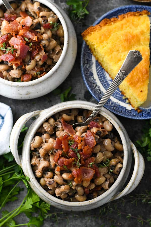Overhead shot of two bowls of New Years black eyed peas on a table with cornbread